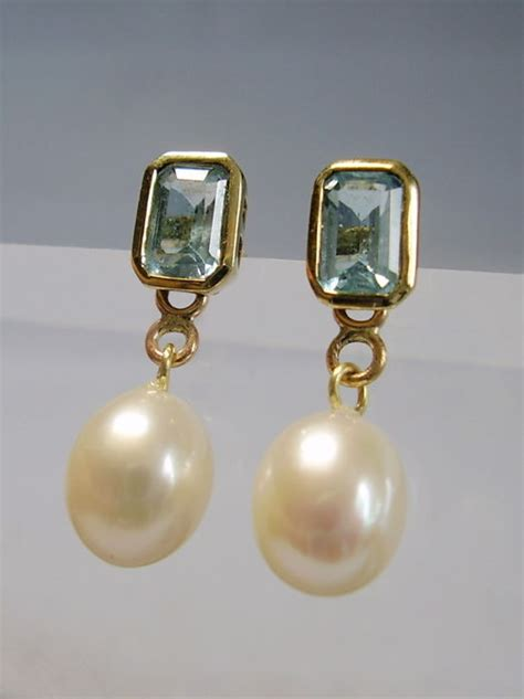 Golden stud earrings with natural blue topazes in emerald