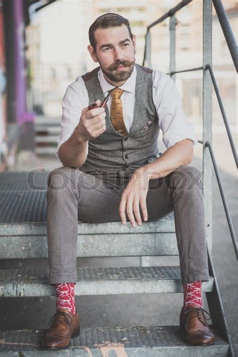 Handsome big moustache hipster man smoking pipe in the